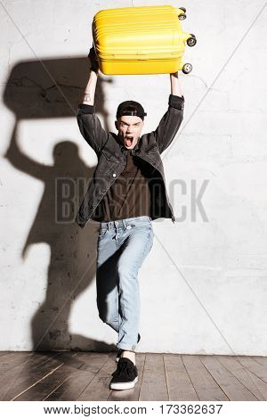 Vertical image of Screaming Hipster in snap back holding suitcase overhead and looking at camera