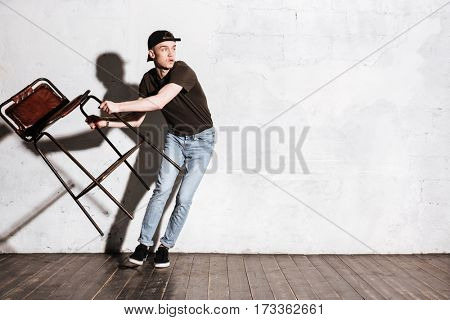 Hipster in snap back holding chair in hands and