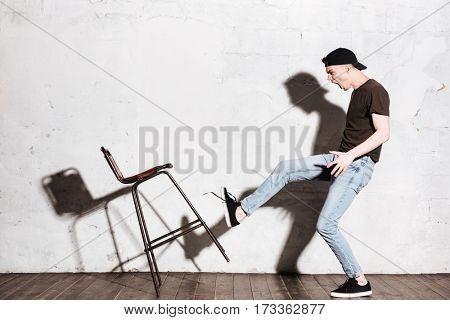 Hipster in snap back kicking chair. Full length portrait. Side view