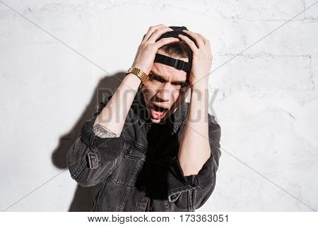Screaming Hipster in snap back holding his head and looking at camera over gray background
