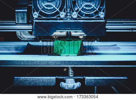 3D printer works and creates an object from the hot molten plastic close-up. Automatic three dimensional 3d printer performs plastic green colors modeling in laboratory.