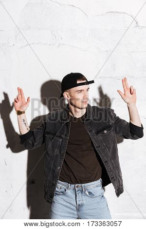 Vertical image of Hipster in snap back with gun gestures looking away over gray background