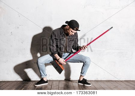 Full length image of Hipster in snap back playing on mop