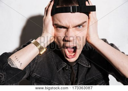 Close up portrait of Screaming Hipster in snap back holding his head and looking at camera over gray background