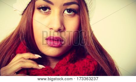 Winter clothing fashion concept. Closeup of young mulatto woman wearing red woolen scarf. Mixed race girl in wintertime clothes studio shot