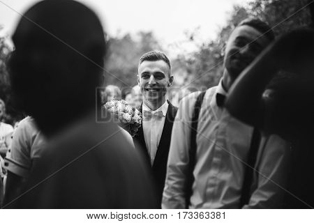 Handsome Happy Brunette Groom In Stylish Black Suit With White Roses Wedding Bouquet Walking To Offi