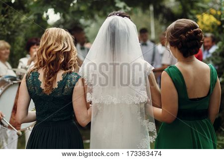 Beautiful Brunette Bride Under Veil In White Wedding Dress Walking With Two Gorgeous Bridesmaids In