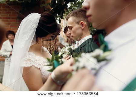 Beautiful Bride In Vintage Wedding Dress Putting On Boutonniere On Handsome Groom And His Stylish Gr