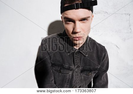 Serious hipster in snap back and jeans shirt looking at camera