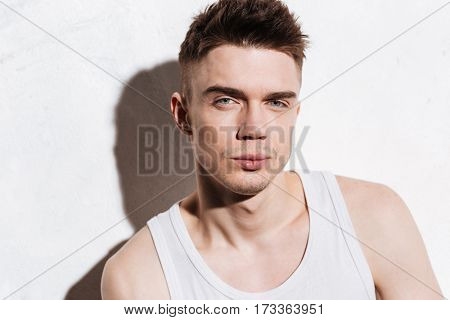 Portrait of confident attractive young man looking at camera over white background