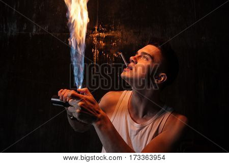 Photo of young man standing on floor with gas spray and cigarette posing isolated over wall background. Looking aside.