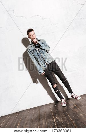 Image of young handsome man standing on floor make silence gesture posing isolated over wall background.
