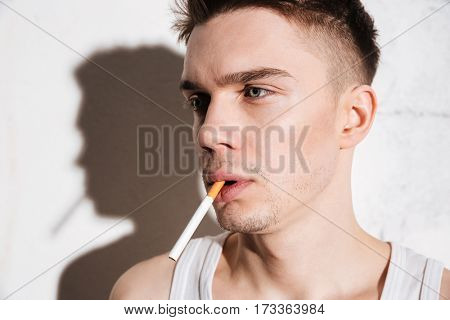 Image of young attractive man standing on floor with cigarette posing isolated over wall background. Looking aside.