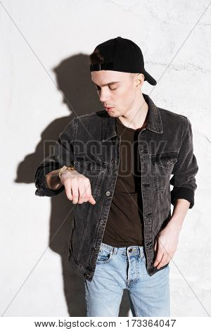 Photo of young man standing on floor looking at watch posing isolated over wall background.