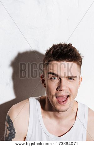 Cheerful joyful young man winking and having fun over white background