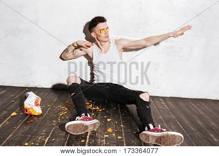 Amusing young man putting potato chips on his eyes and having fun over white background