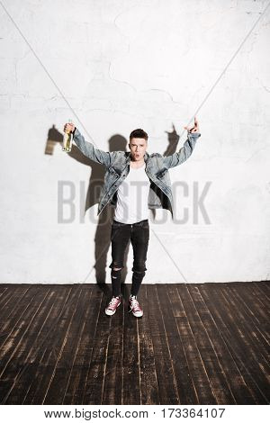 Full length of happy attractive young man drinking champagne and having fun over white background