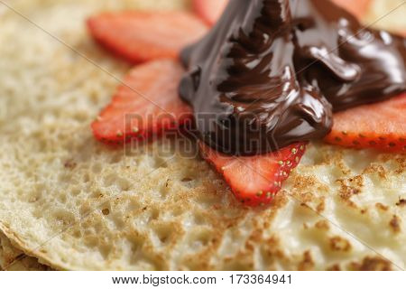 premium dark chocolate poured on blinis with strawberry, shallow focus
