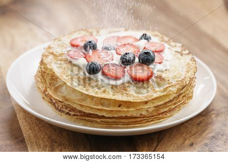 sugar powder fall on fresh blinis or crepes with fresh berries and cream, sweet food