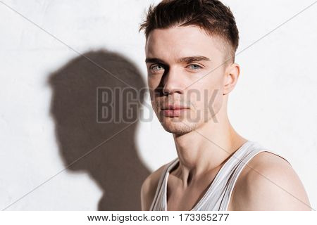 Closeup of attractive confident young man looking at camera over white background