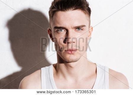 Portrait of serious handsome young man with blue eyes over white background