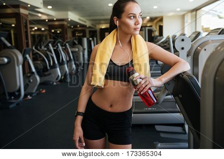 Image of young attractive sports lady standing indoors at gym while listening music. Holding water.