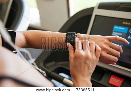 Cropped image of young sports woman make sport exercises indoors at gym while listening music looking at watch.