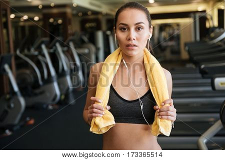 Photo of young amazing sports lady standing indoors at gym while listening music.