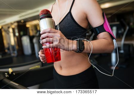 Cropped photo of young sports woman make sport exercises indoors at gym while listening music. Holding water.