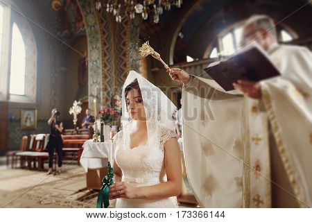 Beautiful Brunette Bride Praying Under Veil In White Wedding Dress,  While Holding Candle During Cer