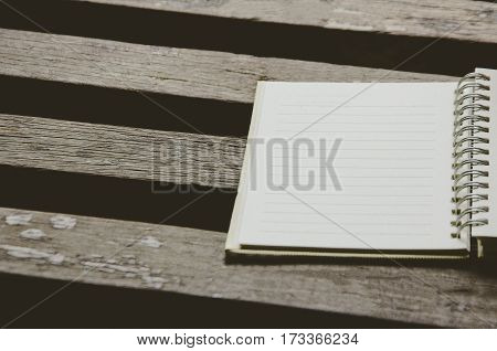 Vintage style . A blank notebook page on wood table. Top view with copy space.