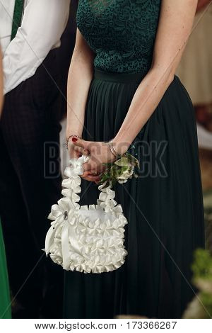 Gorgeous stylish bridesmaid in elegant green dress with boutonniere holding vintage white purse during wedding ceremony in christian church closeup