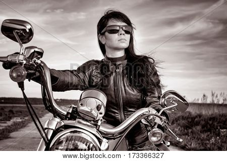 Biker girl in a leather jacket on a motorcycle in black and white