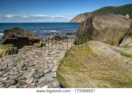 Beach with large boulders at low tide. Boulders covered with algae. In the background you can see the sea. Near the Lynton and Lynmouth villages. North Devon Coast. UK