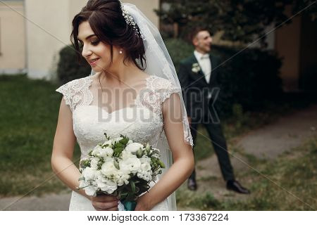 Gorgeous Brunette Bride In Elegant White Wedding Dress And With White Roses Bouquet Smiling, Posing