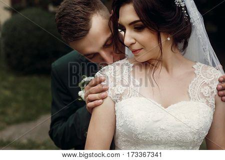 Sensual Handsome Groom In Dark Green Suit Kissing Beautiful Brunette Bride In Stylish White Wedding