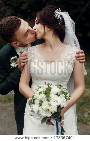 Gorgeous Brunette Bride In Lace White Wedding Dress Kissing Handsome Happy Groom In Stylish Suit, Ne