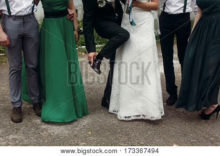 Stylish Wedding Bride Groom With Groomsmen And Bridesmaid Posing At Wedding Reception. Guests Toasti