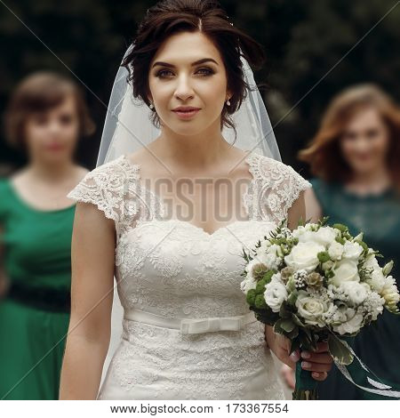 Beautiful Brunette Bride In Vintage White Wedding Dress With Fresh White Roses Bouquet Walking With