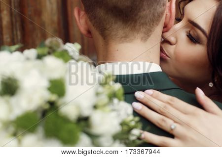 Portrait Of A Beautiful Couple Of Newlyweds, Gorgeous Brunette Bride In White Dress Kissing Handsome