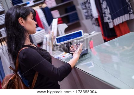 Girl pays to shop using mobile phone. NFC - Near field Communication. Mobile payment PayPass.