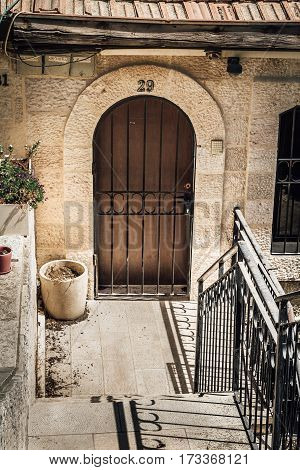 JERUSALEM ISRAEL - OCTOBER 3: The arched door with metal lattice of white stone house the historic neighborhood Yemin Moshe in Jerusalem Israel on October 3 2016