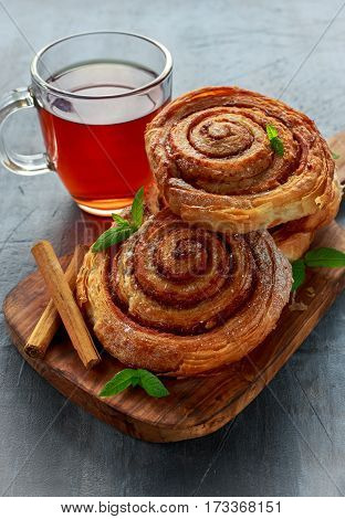 Freshly Baked Traditional Sweet Cinnamon Rolls, Swirl with hot black Tea and mint.