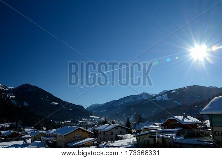 Wagrain Austria - January 28 2017: Buildings mountains sky and sun in Wagrain in Alps in Austria.