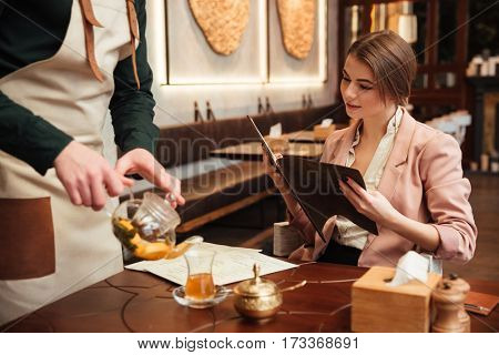 Image of attractive pretty young woman sitting in cafe. Looking at menu list.