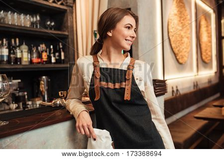 Picture of amazing young woman bartender standing in cafe. Looking aside.