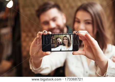 Photo of amazing young loving couple sitting in cafe and take a selfie by phone.
