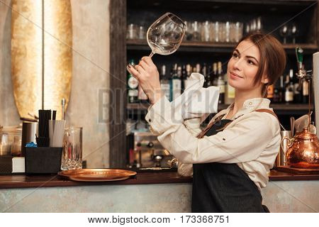 Picture of cheerful young woman standing in cafe wipe a glass. Looking aside.