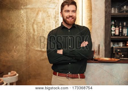 Photo of cheerful young bearded man standing with arms crossed in cafe. Looking aside.