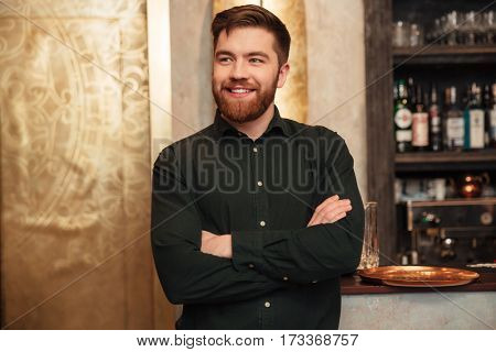 Image of happy young bearded man standing with arms crossed in cafe. Looking aside.